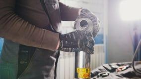 Samochodowy mechanik nalewa motorowego olej dla samochodu przy remontową stacją obsługi zdjęcia stock