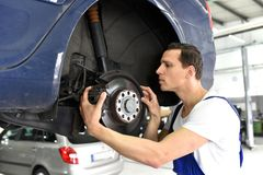 Samochodowy mechanik naprawia hamulce pojazd na podnośnej platformie obraz stock