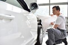 Samochodowy mechanik naprawia samochodowego bodywork pojazd po ruchu drogowego a zdjęcie royalty free
