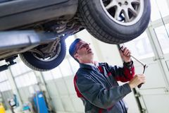 Samochodowy mechanik pracuje przy automobilowym usługowym centrum zdjęcie stock