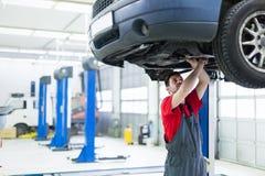 Samochodowy mechanik pracuje przy automobilowym usługowym centrum fotografia royalty free