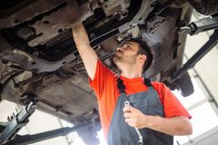 Samochodowy mechanik pracuje przy automobilowym usługowym centrum zdjęcia royalty free