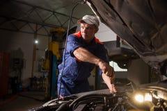 Samochodowy mechanik pracuje w auto remontowej usługa Naprawianie samochodu używać obraz stock