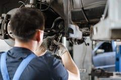 Samochodowy mechanik sprawdza samochodowego koło i naprawy zawieszenia szczegół Podnoszący samochód przy remontową stacją obsługi zdjęcie royalty free