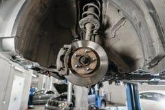 Samochodowy mechanik sprawdza samochodowego koło i naprawy zawieszenia szczegół Podnoszący samochód przy remontową stacją obsługi zdjęcia royalty free