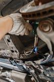 Samochodowy mechanik sprawdza samochodowego koło i naprawy zawieszenia szczegół Podnoszący samochód przy remontową stacją obsługi obraz royalty free