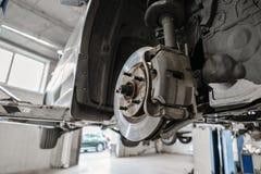Samochodowy mechanik sprawdza samochodowego koło i naprawy zawieszenia szczegół Podnoszący samochód przy remontową stacją obsługi obrazy stock