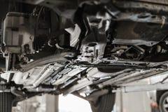 Samochodowy mechanik sprawdza samochodowego koło i naprawy zawieszenia szczegół Podnoszący samochód przy remontową stacją obsługi obraz stock