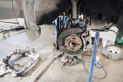 Samochodowy mechanik sprawdza samochodowego koło i naprawy zawieszenia szczegół Podnoszący samochód przy remontową stacją obsługi zdjęcie stock