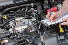 Samochodowy mechanik sprawdza samochodowego silnika zdjęcia royalty free