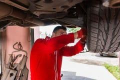 Samochodowy mechanik w mundurze naprawia koło podczas gdy pracujący underne obraz stock