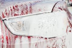 Samochodowy obmycie z kontakt pianą, reflektor z gęstym piankowym zakończeniem obrazy stock