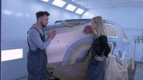 Samochodowy obraz, auto mechanicy mężczyźni i kobieta, wybieramy kolor malować pojazd podczas remontowej pracy zbiory