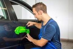 Samochodowy opakunkowy specjalista zawija samochodową drzwiową rękojeść z adhezyjną folią lub filmem Obrazy Royalty Free