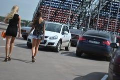 Samochodowy parking w ras dziewczynach iść w krótkich spódnicach Sportscar strojeniowe rywalizacje na nastrajających samochodach  Obrazy Stock