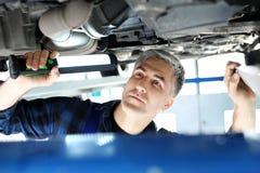 Samochodowy remontowy sklep, mechanik naprawia samochód Zdjęcia Stock