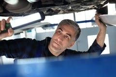 Samochodowy remontowy sklep, mechanik naprawia samochód Obraz Stock