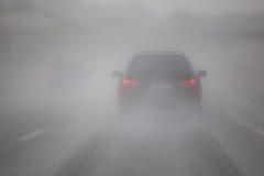 Samochodowy ruch drogowy z mgłą i deszczem Obraz Stock
