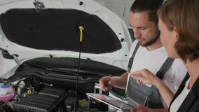 Samochodowy ` s mistrz pokazuje technicznego warunku samochód na pastylce, Auto repairman przedstawienia na awaria pojazdzie, aut zbiory wideo