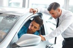 Samochodowy sprzedaż konsultant Pokazuje Nowego samochód Potencjalna nabywca w S Obrazy Stock