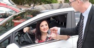 Samochodowy sprzedawca daje samochodów kluczom młoda kobieta Obraz Royalty Free