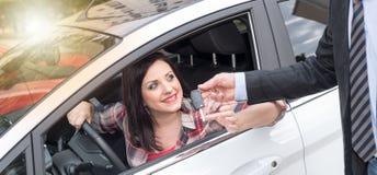 Samochodowy sprzedawca daje samochodów kluczom młoda kobieta, lekki skutek Zdjęcia Stock