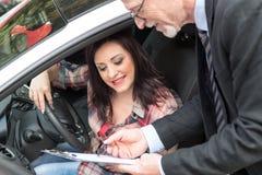 Samochodowy sprzedawca daje wyjaśnieniom na schowku młoda kobieta Fotografia Stock