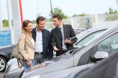 Samochodowy sprzedawca pokazuje pojazdy klienci Obraz Stock