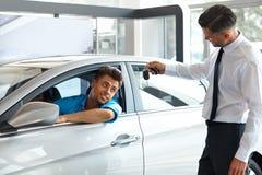 Samochodowy sprzedawca Wręcza nad nowym samochodu kluczem klient przy sala wystawową Zdjęcie Stock