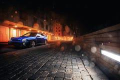 Samochodowy Subaru Impreza WRX stojak w Moskwa mieście blisko nowożytnych budynków przy nocą Zdjęcie Stock