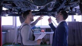 Samochodowy utrzymanie, mechanik z schowek inspekcji warunku technicznym samochodem i radzi klienta pod pojazdem zdjęcie wideo