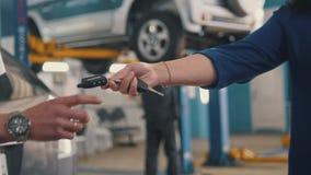 Samochodowy warsztat - kobieta daje kluczom samochód dla mechanika Fotografia Royalty Free