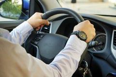 Samochodowy wnętrze z męskim kierowcy obsiadaniem za kołem, miękki zmierzchu światło Luksusowa pojazd deska rozdzielcza, elektron Zdjęcie Stock