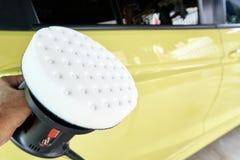 Samochodowy wyszczególniać pracownika ` s ręka używać polerować i nawoskować w gar Zdjęcia Royalty Free