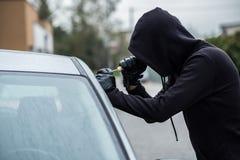 Samochodowy złodziej próbuje łamać w samochód z śrubokrętem Fotografia Royalty Free
