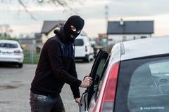 Samochodowy złodziej wchodzić do pojazd i kraść samochód Fotografia Stock