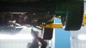 Samochodu diagnostyk - mechanik pracuje pod podnoszącym samochodem, skupiający się tło zdjęcie wideo