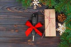 Samochodu klucz z kolorowym łękiem z prezenta pudełkiem na drewnianym tle Zdjęcia Stock