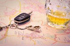 Samochodu klucz z wypadkowym i piwnym kubkiem na mapie Obrazy Stock