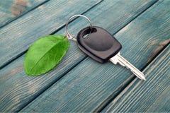 Samochodu klucz z zielonym liściem na drewnianym tle Fotografia Royalty Free