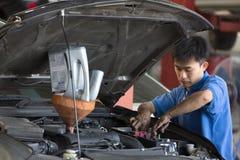 Samochodu mechanik egzamininuje samochodowego zawieszenie podnoszący samochód obrazy royalty free