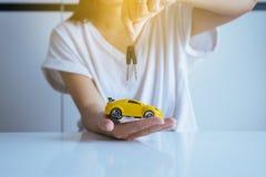 Samochodu model na ręce z samochodów kluczami, biznesem i finanse pojęciem, zdjęcia stock