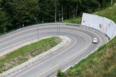 Samochodu osobowego pivoting ruch przy asfaltową halną hairpin drogą, widok z lotu ptaka zdjęcie royalty free