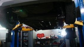 Samochodu samochodowy diagnostyk - mechanik pracuje pod podnoszącym samochodem, suwak zbiory wideo