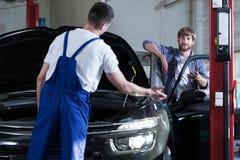 Samochodu usługowy pracownik diagnozuje samochód Zdjęcie Royalty Free