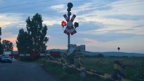 Samochody czeka przy linii kolejowej rozblaskowego naprzemianległego czerwonego światła skrzyżowaniem - półmroku czas zbiory wideo