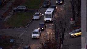 Samochody iść na ulicie przy półmrokiem zdjęcie wideo