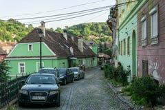 Samochody i domy na ulicach średniowieczny miasteczko Sighisoara, Rumunia Antyczni budynki i uliczne kawiarnie fotografia stock