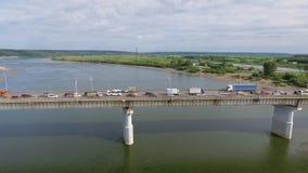 Samochody jadą przez most przez rzekę i miasto zbiory