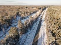Samochody na drodze w zimie z śniegiem zakrywali drzewa widok z lotu ptaka fotografia stock